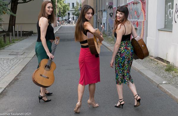 Die drei Musikerinnen von OVNI Tango gehen mit ihren Gitarren auf den Horizont zu und blicken dabei zurück in die Kamera.