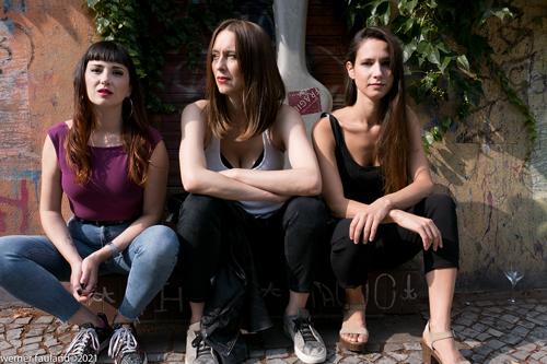 Die drei Musikerinnen von OVNI Tango sitzen vor einem Gebäude auf einer Treppenstufe